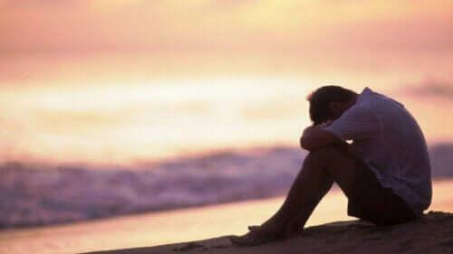 En ledsen man som sitter vid stranden och tänker på yttre känsloreglering