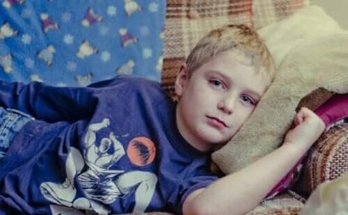 En ledsen pojke som ligger på soffan
