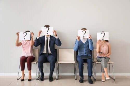 En grupp människor som håller en skylt med ett frågetecken framför deras ansikten