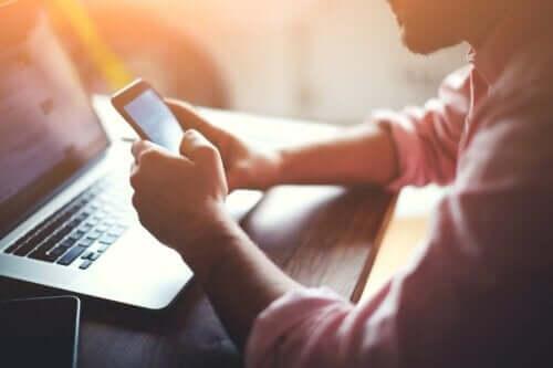 En man som kotrollerar sina sociala medieplattformar på sin telefon