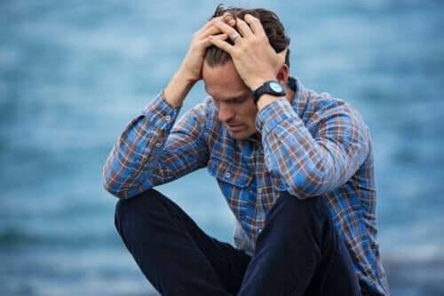En orolig man som sitter vid havet