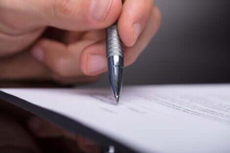 En närbild på en hand, en penna och ett formulär