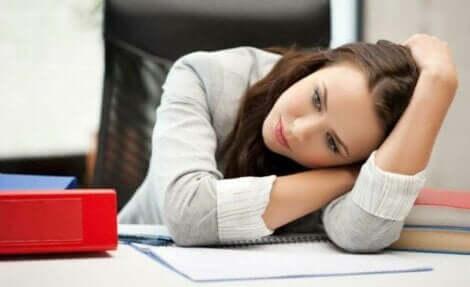 En trött kvinna vilar huvudet på ett skrivbord