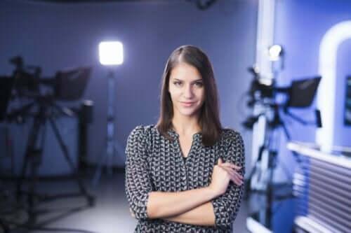 En TV-programledare som ler mot kameran