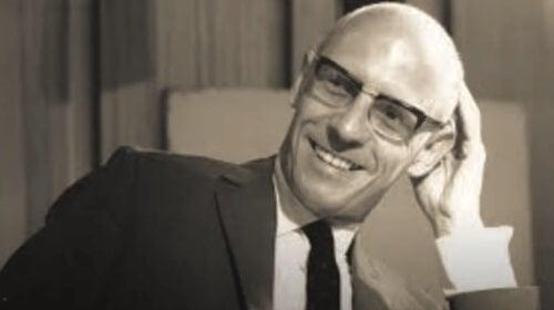 En svartvit bild av Michel Foucault: han ler