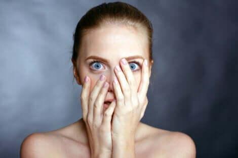 En kvinna med blåa ögon som täcker sitt ansikte