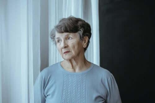 En äldre dam står och tänker vid ett fönster