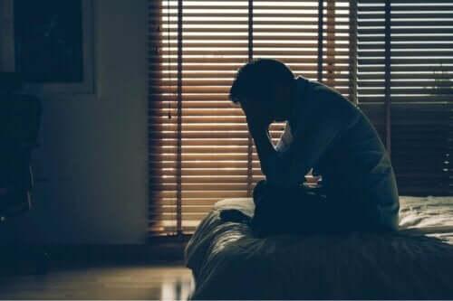 En nödställd man sitter ensam i en säng, i ett mörkt rum, med huvudet i händerna