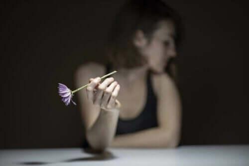 En kvinna som håller en blomma