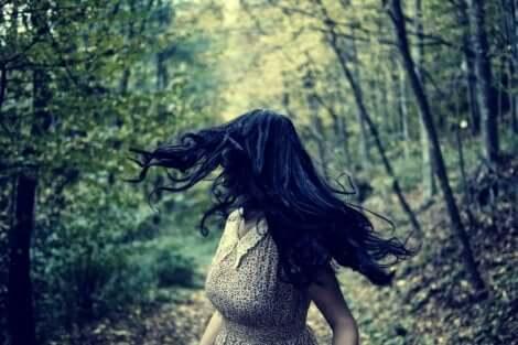 En långhårig kvinna som flyr genom skogen.