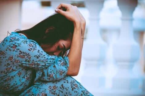En kvinna är hopkrupen med upplevda känslor och fysisk smärta