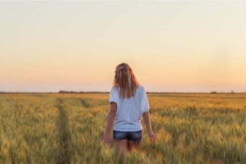En kvinna vandrar på ett vetefält
