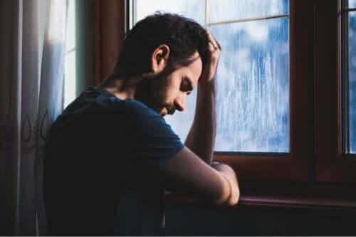 En ledsen man som står vid ett fönster