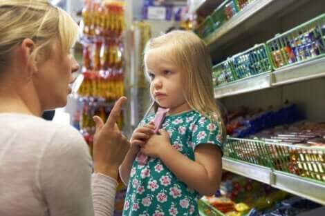 En liten flicka vill ha chocklad i mataffären