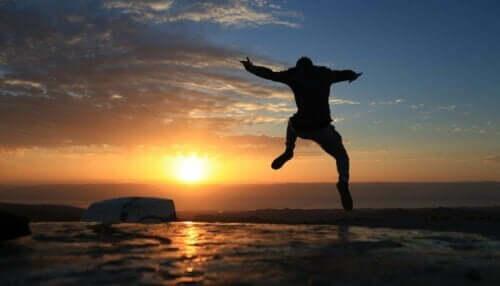 En kille hoppar av glädje framför solnedgången