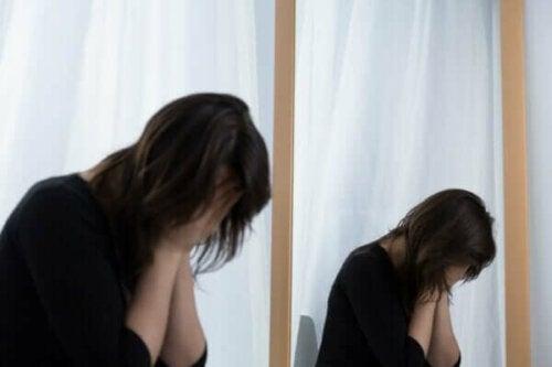En förtvivlad kvinna döljer ansiktet i händerna