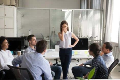 En generad kvinna framför sina medarbetare