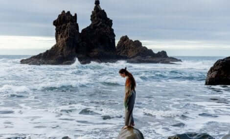 En kvinna som står på en stenbumling vid havet