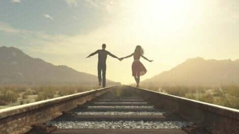 Ett lyckligt par som går längst ett tågspår