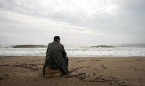En äldre man sitter på en gråmulen dag vid havet