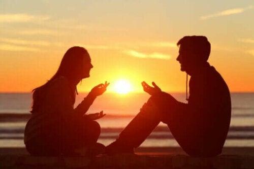 Två personer sitter vid havet och pratar med solnedgången som bakgrund