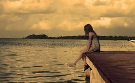 En flicka som sitter på en brygga