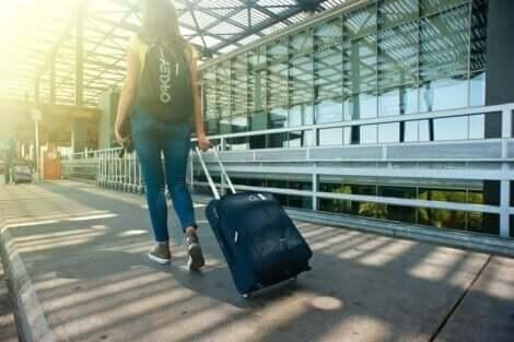 En kvinna som rullar en resväska och upplever rädslan för att resa