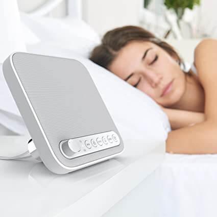 Vitt brus kan hjälpa människor att sova bättre:En kvinna som sover genom att använda en maskin med vitt brus.