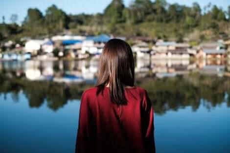 En kvinna som ser över en sjö mot en liten by