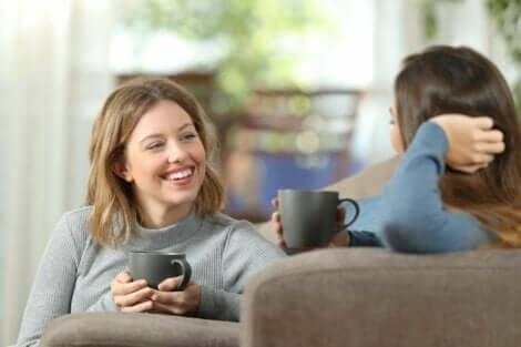 Två kvinnor som dricker kaffe och pratar i en soffa