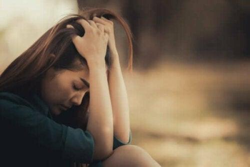 En ledsen kvinna tänker på sörjandets fyra uppgifter