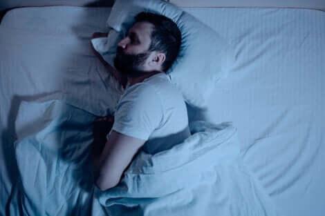 En man sover på sidan i sin säng