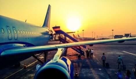 Folk som går ombord på ett plan vid solnedgången
