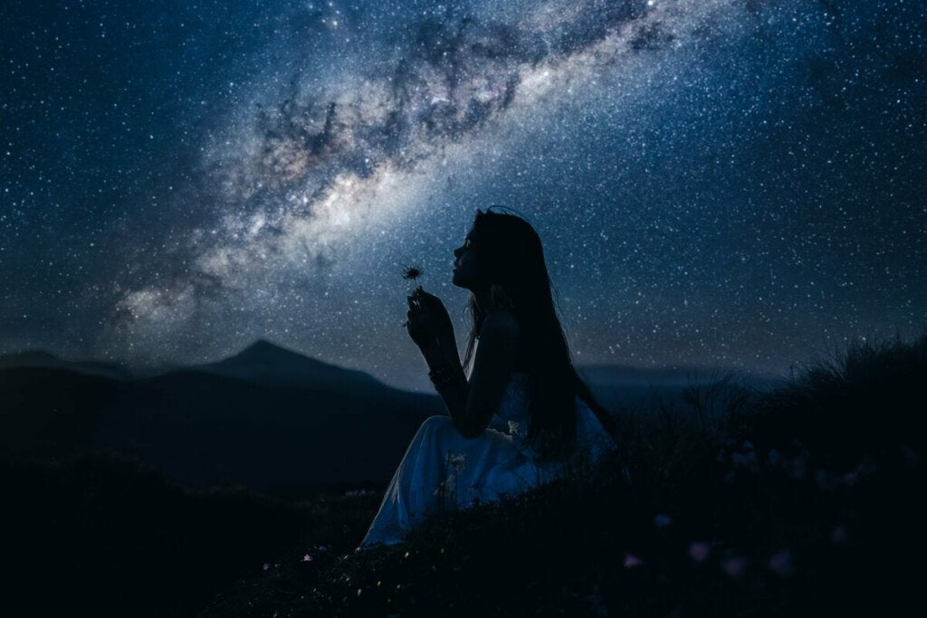 En kvinna med en blomma i natten