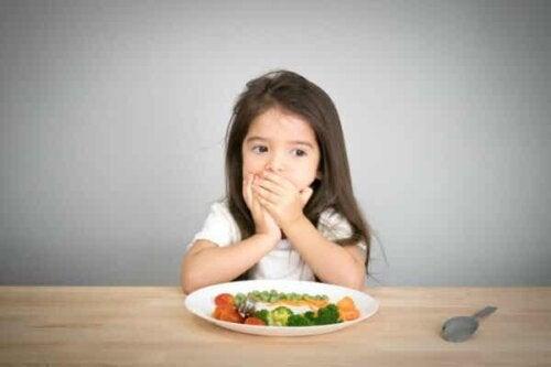 En flicka täcker munnen framför en tallrik med grönsaker