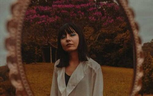 En kvinna som andas djupt, i en park, framför en spegel
