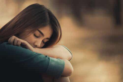 En kvinna med slutna ögon och huvudet i armarna