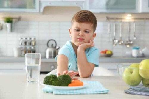 En pojke skjuter undan en tallrik med broccoli och morötter