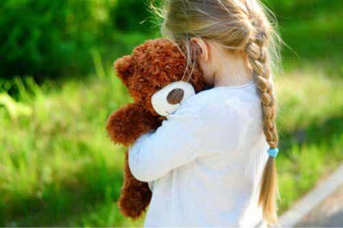 En flicka som kramar sin nallebjörn