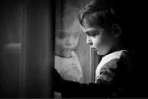 En ledsen pojke som ser ut genom fönstret