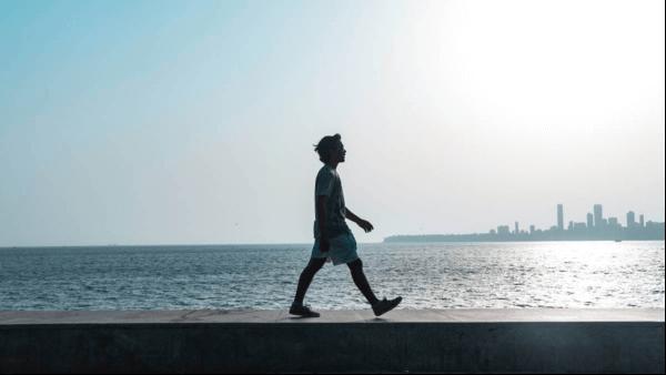 En man som går längs havet