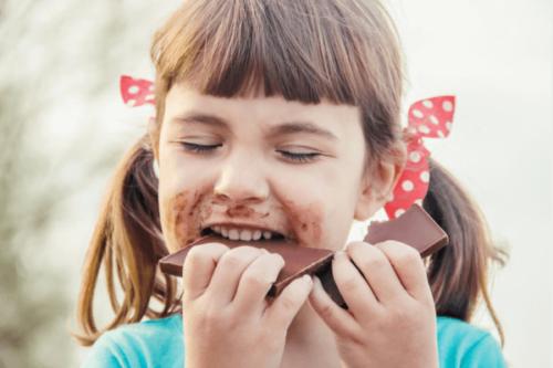 Flicka som äter choklad