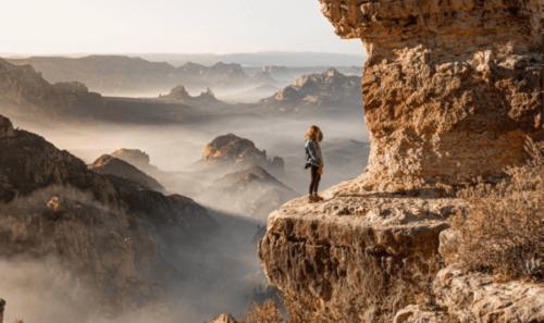 En kvinna som står på kanten av en klippa.